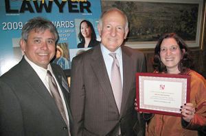 Minouche Kandel, right, holds up her attorney of the year award from the California Lawyer magazine. With her are Ramon Arias, executive director of Bay Area Legal Aid, left, and Ronald M. George, Chief Justice of the California Supreme Court.